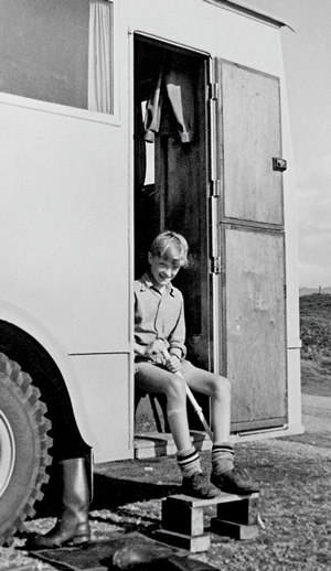 Stefan Sykut, as a young boy, sits in the door of his grandfather's wooden RV.