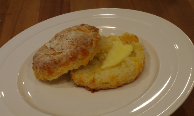 A buttered buttermilk biscuit sits on a plate.