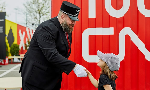 CN conductor shaking hands with young girl.