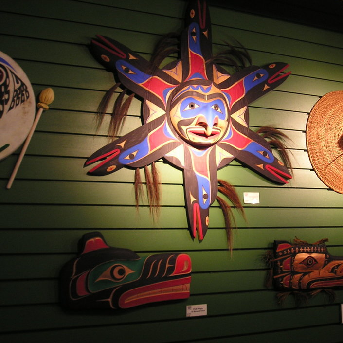 The Sun Mask, a piece by Wilson George, is surrounded by other works of art.