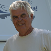 Fit-looking senior man with two bicycles and a travel trailer in the background