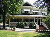 Photo of a beautiful historic house with a large white front porch, awnings and gable windows.