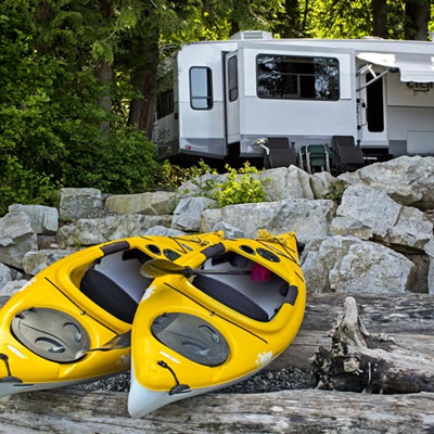 Two yellow kayaks sitting on beach, with camper parked in background.