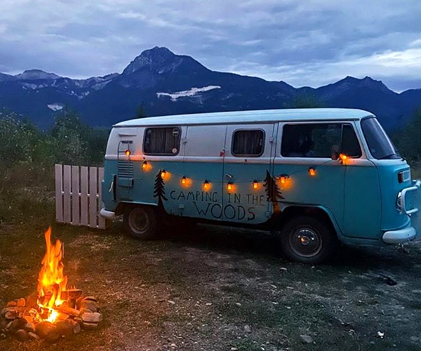 Blue and white VW van with picket fence and campfire.