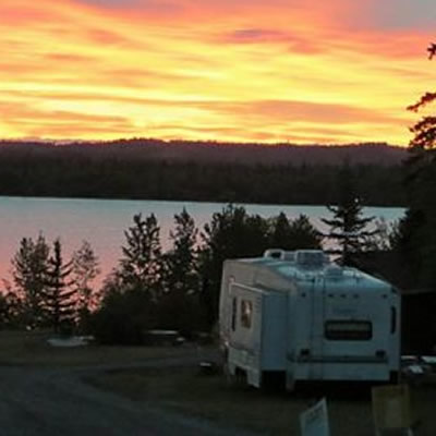 Camper parked in spot overlooking lake as sun sets.