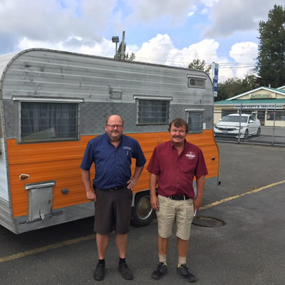 The two sons of Kustom Koach founder Carl Carstensen standing in front of trailer.