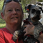 Woman holding small dog stands beside her RV unit.