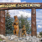 wooden carvings of bears under a welcome to Chetwynd sign