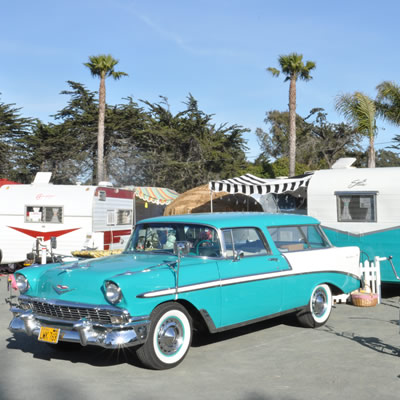 A 1956 tropical turquoise Chevrolet Bel Air along with a matching 1961 Shasta Compact travel trailer.