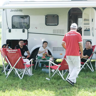 Group of people sitting outside in front of motorhome.