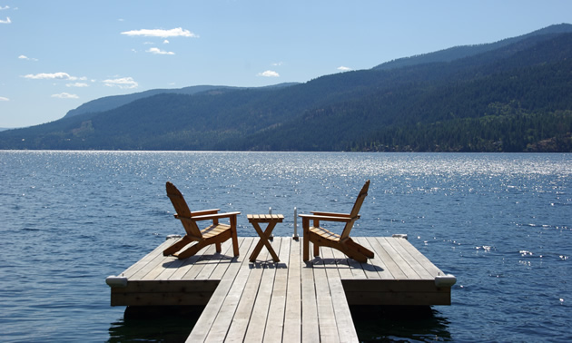 Two lounge chairs await on a dock extending over Christina Lake, B.C.