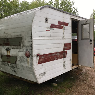 Picture of trailer, with red stripes and damage on back end.