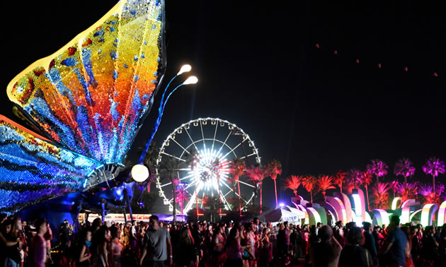 Large group of festival goers at night, with lit-up Ferris wheel in background and large, colourful illuminated butterfly sculpture in foreground.