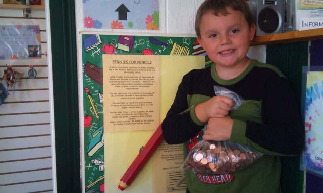 Young boy holding a bag of pennies