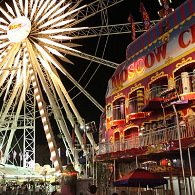 Carnival with ferris wheel, lit up at night.