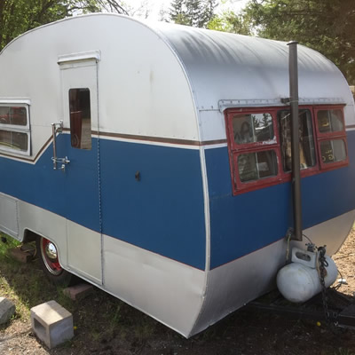 A blue and white Cozy Cruiser trailer.