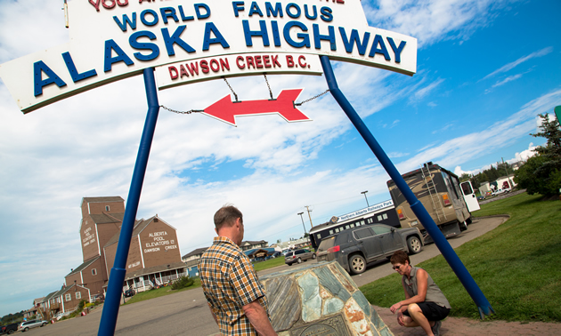 A couple look at the Mile 0 cairn for the Alaska Highway, found in Dawson Creek.