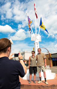 A couple takes a picture at the Mile 0 post of the Alaska Highway in Dawson Creek.