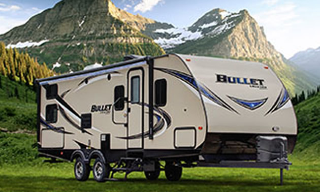 Fifth wheel RV sitting in front of scenic mountain view.