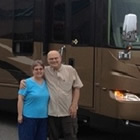 A man stands with his arm around his wife who is wearing a blue shirt in from of a large RV in shades of brown.