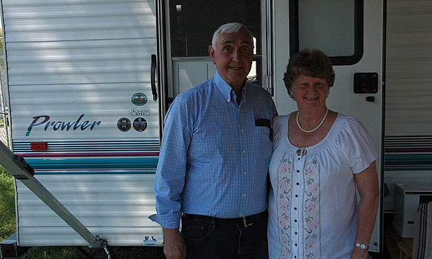 Elderly couple standing beside their RV