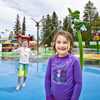 A little boy and girl smile at the camera from  brightly coloured spray park.