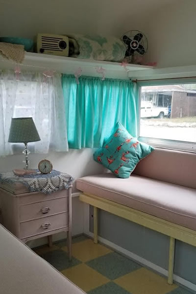 Interior of trailer, with turquoise and pink decor, checkered floor.