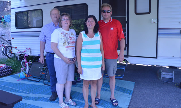 Two couples in summer clothing stand beside a motorhome
