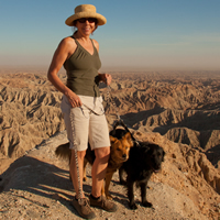 Woman and two dogs on a high ridge overlooking barren badlands
