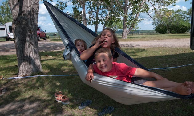 These three cousins are enjoying grandma's homemade cookies in a hammock.