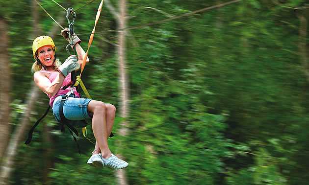 lady sliding down a zipline like the one that will be added in Fernie BC