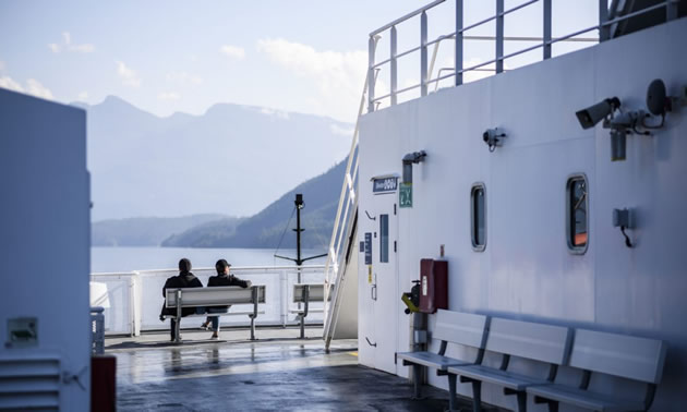 Two people sitting on bench on deck of ferry.