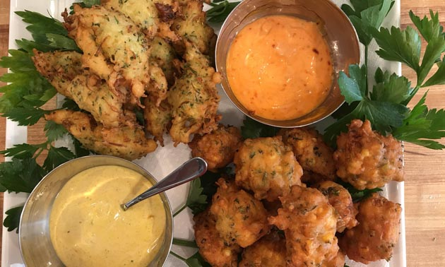 Plate of fritters and dishes of sauce.