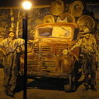 a painted mural on the side of a building at night lit by a vintage streetlight; mural is of two men standing beside an old truck