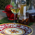 Attractive red and yellow designs on china is set out in front of ice tea, an apple, and glasses of wine to create an appealing camp setting.