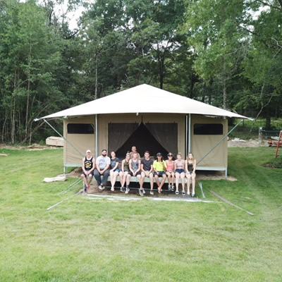 The O'Neill's Millennial tent building crew sit on the front porch of one of their seven recently installed Eco Tents, which feature electricity and running water.