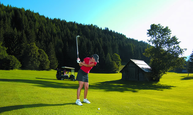 A woman golfing with treed hillside in background.