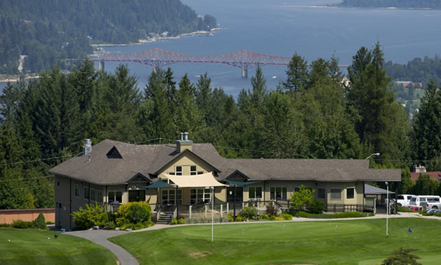 View of golf club house on hill, with lake in background.