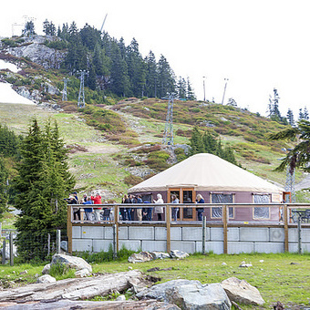 Tourists standing on the porch of the yurt lookout at Grouse Mountain