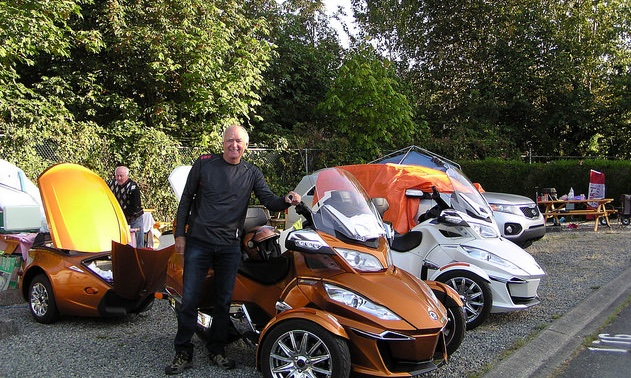 François Guite standing next to his Spyder that brought him from Quebec to Vancouver