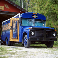 Bob and Carol Braisher stand outside of their converted school bus, fondly named Gus the Bus.