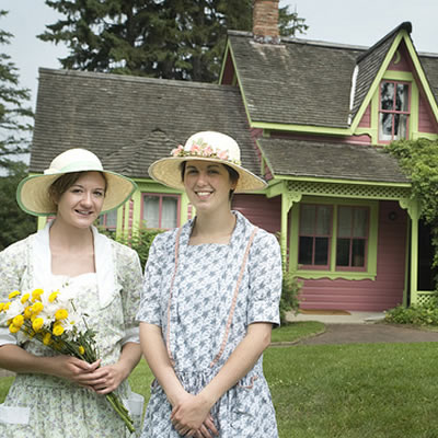 Hisotric house, with two ladies dressed in period costume in the foreground, one of them holding a bouquet of yellow daisies.