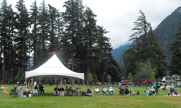 An audience sits beneath an outdoor tent in Hope's Memorial Park.