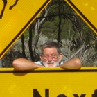 Man poses next to a road sign of a camel, a kangaroo and a wombat in Australia