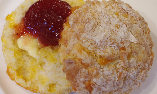 A buttermilk biscuit with strawberry jam and butter looks tasty.