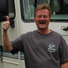 Smiling man does a thumbs-up, standing in front of his motorhome.