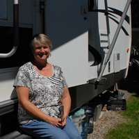 A woman sits on the steps leading into her white and black RV. A water dispenser is beside the entrance.