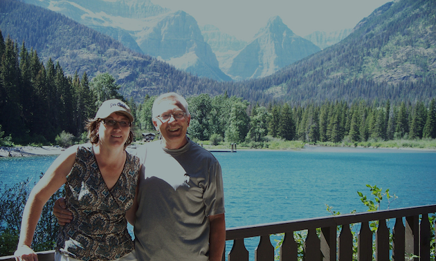 couple standing by an alpine lake