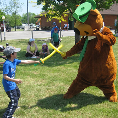 Person in Yogi Bear costume and child sparring with foam swords.