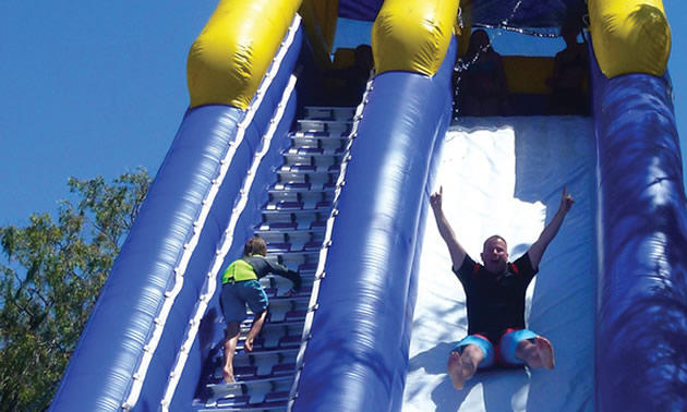 Man and child sliding down inflatable water slide.